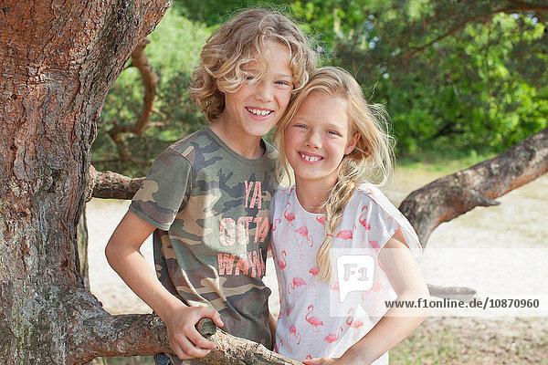 Junge und Mädchen neben dem Baum schauen lächelnd in die Kamera Junge und Mädchen neben dem Baum schauen lächelnd in die Kamera
