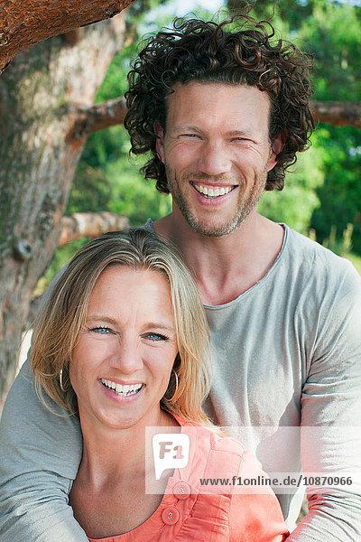 Paar steht am Baum und schaut lächelnd in die Kamera