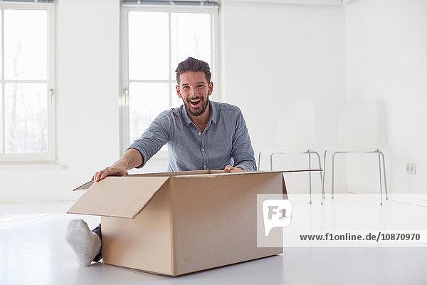 Porträt eines jungen Mannes  der auf dem Boden sitzt und einen Karton im neuen Haus öffnet