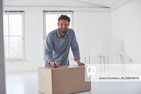 Porträt eines jungen Mannes,  der beim Umzug auf einem Karton schreibt