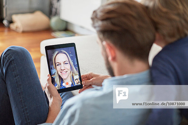 Man and son sitting on floor talking to mother on digital tablet video call