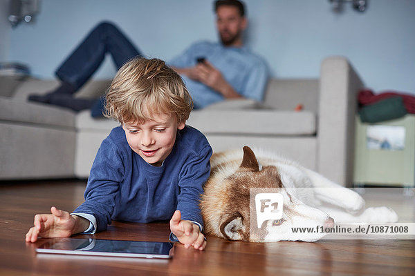 Boy lying on living room floor with husky using digital tablet
