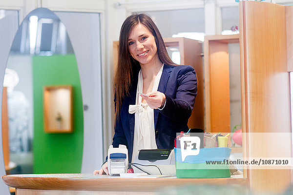 Sales assistant offering credit card smiling