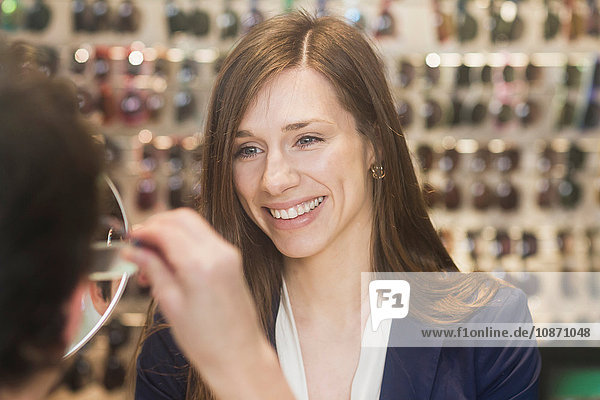 Woman in opticians assisting customer  smiling