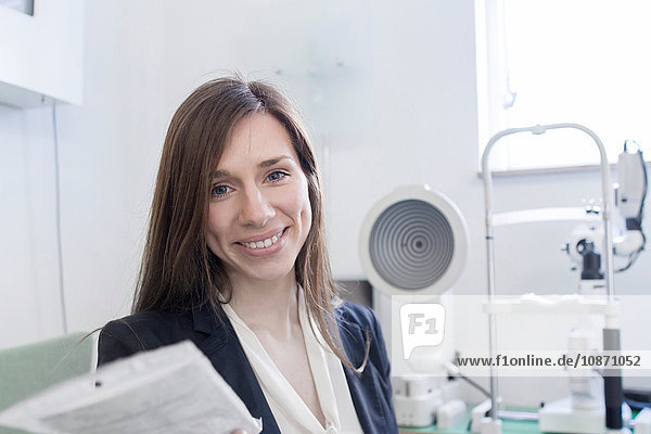 Woman in opticians office looking at camera smiling