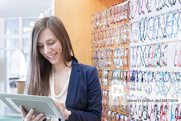 Sales assistant in opticians using digital tablet smiling