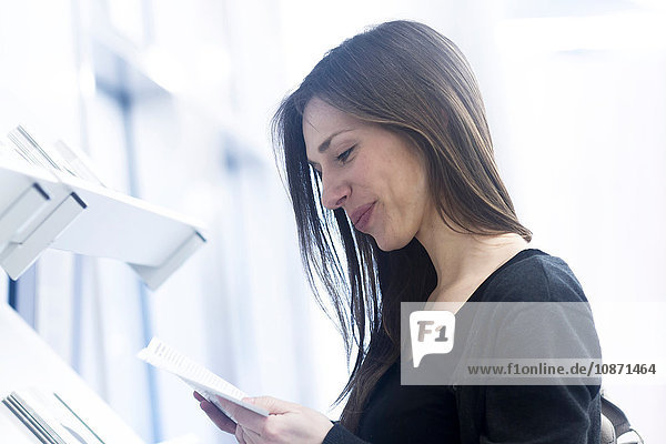 Side view of woman holding paperwork looking down smiling