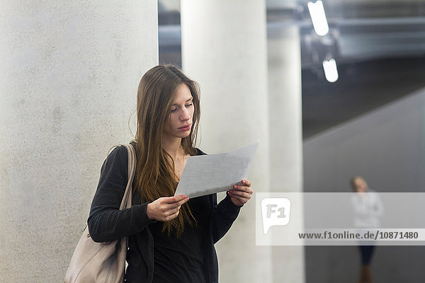 Woman in front of columns looking at paperwork