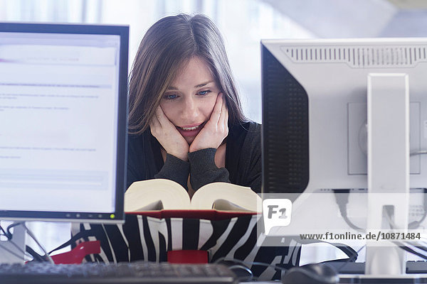Woman sitting at computer chin in hand looking down reading book