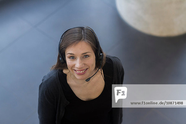 High angle view of woman wearing telephone headset looking at camera smiling