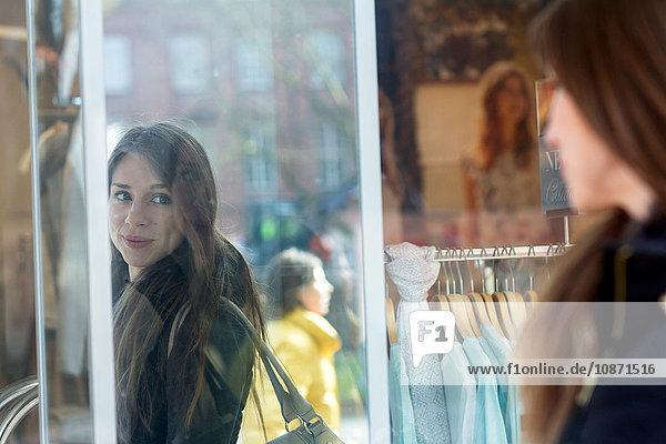Frau mit Handtasche schaut lächelnd in Ladenspiegel