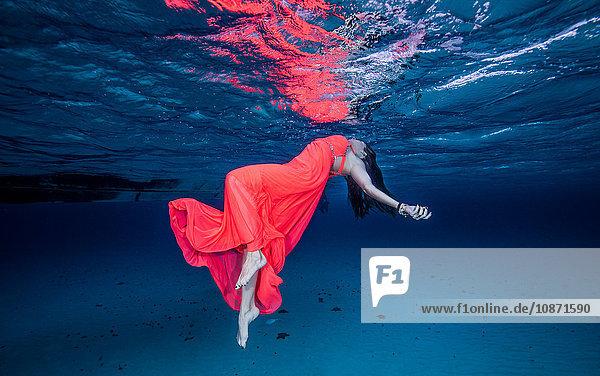 Frau in Rot schwimmt nahe der Meeresoberfläche