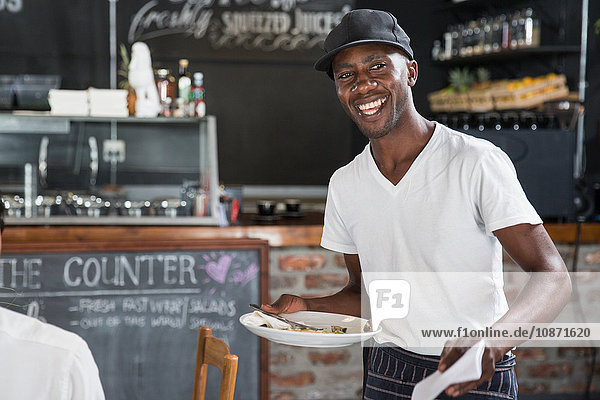 Waiter working in restaurant cleaning tables