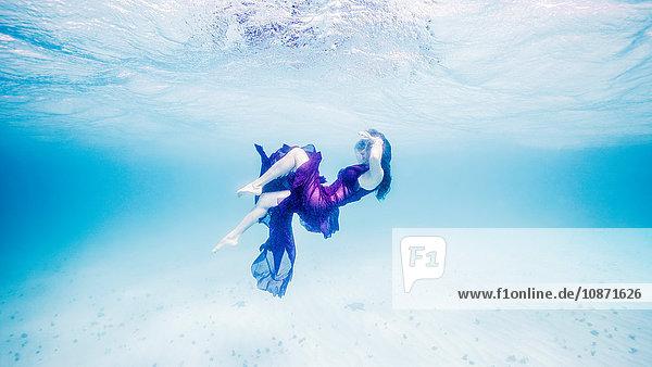 Frau in Lila schwimmt nahe der Meeresoberfläche