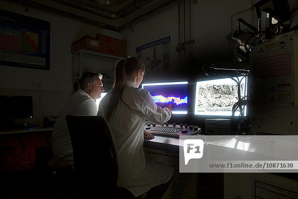 Scientist looking at images from SEM microscope