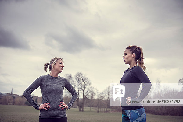 Women wearing sports clothes in field hands on hips face to face smiling