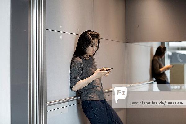 An die Wand gelehnte Frau  die ein Smartphone benutzt