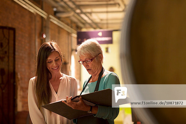 Two women looking at paperwork in wine cellar
