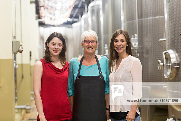 Portrait of three women in wine cellar  smiling