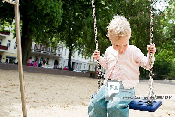Baby girl on swing at park