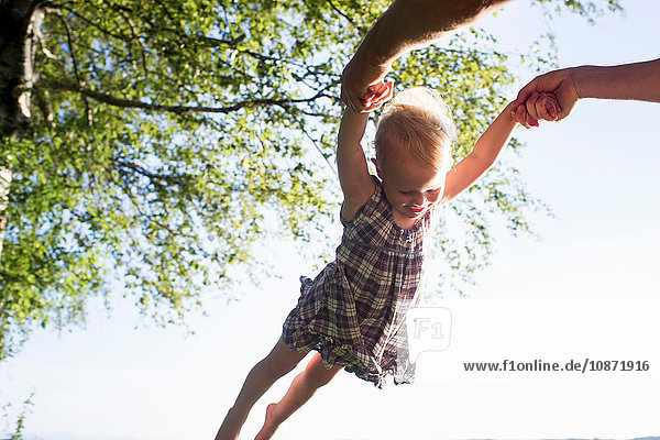Father swinging baby girl in air  outdoors  low angle view