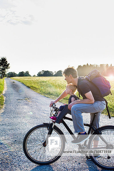 Father and baby daughter riding bike together