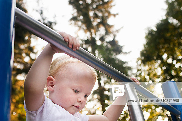 Baby girl on climbing frame at park