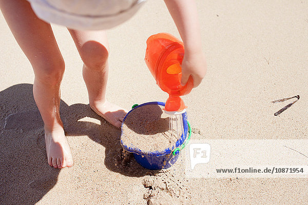 Baby girl pouring water on bucket of sand  elevated view