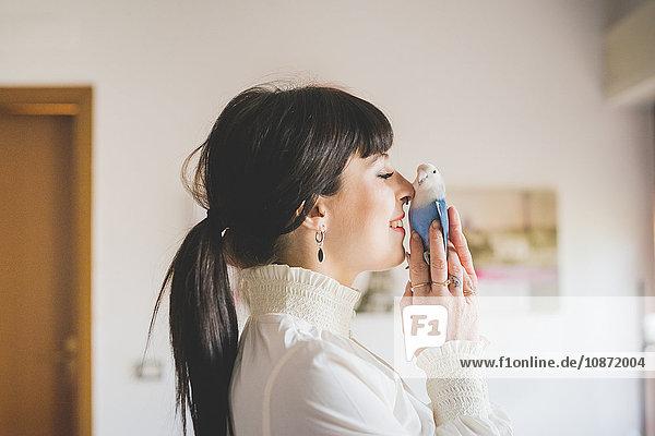 Young woman holding pet bird indoors