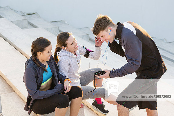Three friends taking a break from exercising  listening to music on mp3 players