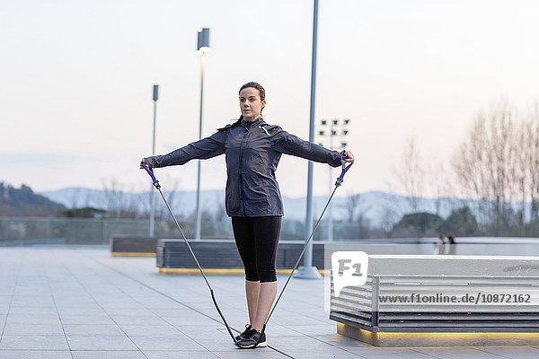 Junge Frau  die sich im Freien bewegt und dabei ein Stretch-Seil benutzt