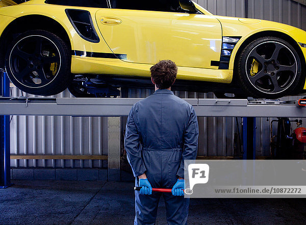 Male mechanic checking yellow sports car  holding socket wrench behind his back  rear view