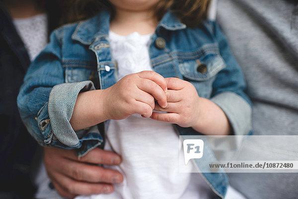Mutter und Vater halten junge Tochter  mittlerer Abschnitt
