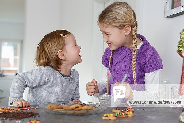 Girls at kitchen counter decorating cookies face to face smiling