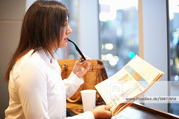 Mature businesswoman reading newspaper at city cafe  Tokyo  Japan