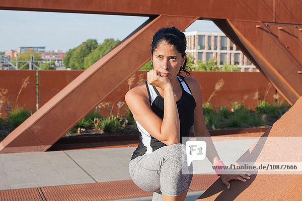 Frau macht Trainingspause auf städtischer Fußgängerbrücke