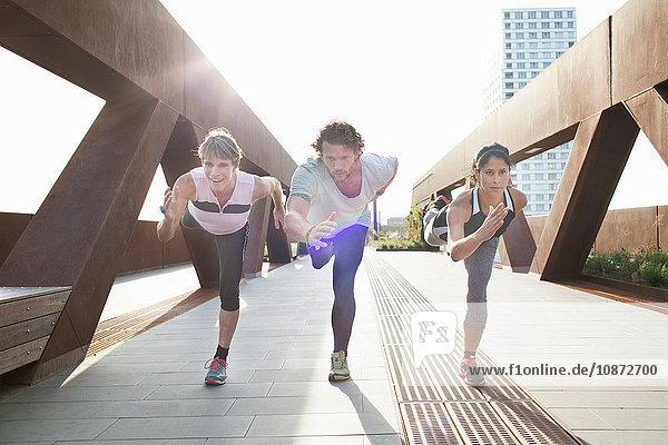 Mann und zwei Frauen trainieren auf einem Bein auf einer städtischen Fußgängerbrücke