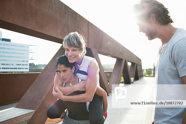 Two women giving piggyback on urban footbridge with male personal trainer