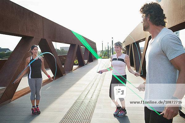 Zwei Frauen springen mit einem männlichen Personal Trainer über die städtische Fußgängerbrücke