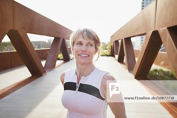 Portrait of mature woman training on urban footbridge