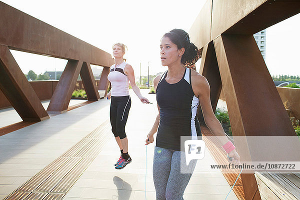 Two women training with skipping ropes on urban footbridge