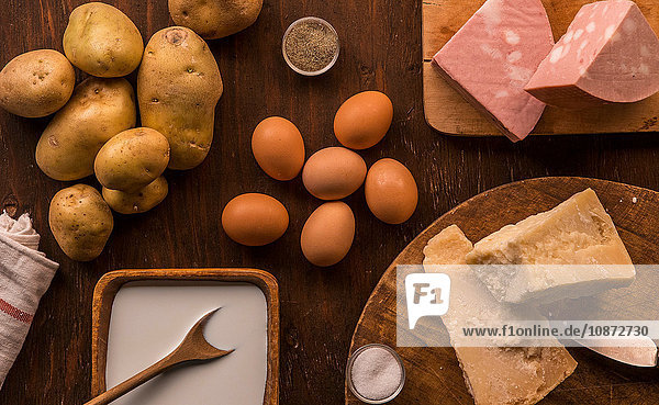 Draufsicht auf rohe und zubereitete Lebensmittel  Parmesan  Milch  Eier und Kartoffeln