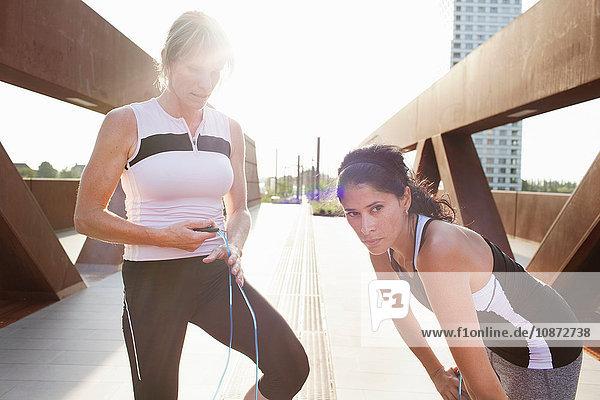 Two women taking a break from skipping rope training on urban footbridge