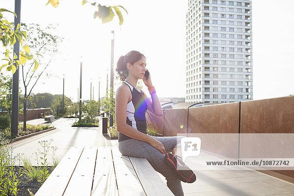 Frau trainiert  sitzt auf einer städtischen Fußgängerbrücke und spricht mit einem Smartphone