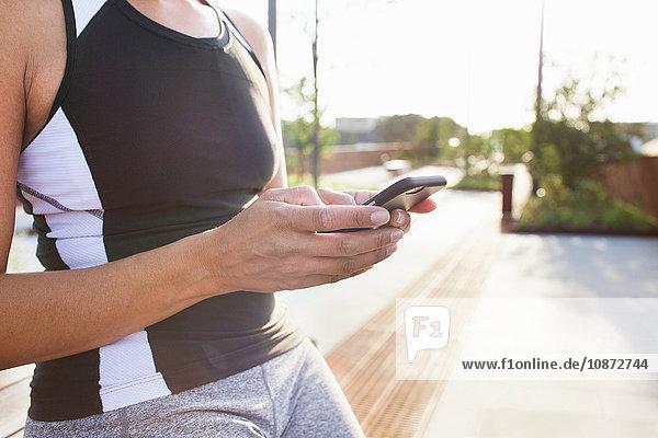 Ausschnitt einer Frau beim Training  auf einer städtischen Fußgängerbrücke beim Lesen von Smartphone-Texten
