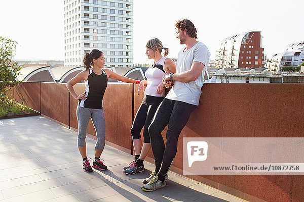 Two women and man training  chatting on urban footbridge