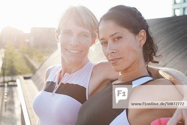Portrait of two female friends training on urban footbridge
