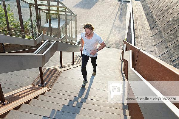 Männlicher Läufer läuft Stadttreppe hinauf