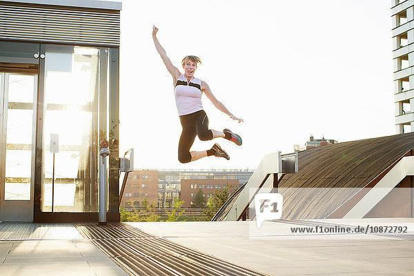 Woman training  jumping mid air on footbridge
