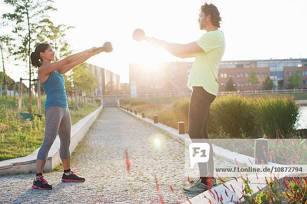 Frau und Personal Trainerin beim Krafttraining mit Kettlebells am Flussufer